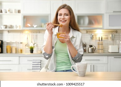 Positive young woman with honey in kitchen