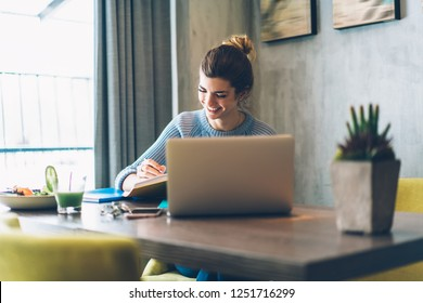Positive young woman laughing and doing homework to prepare for studying seminar sitting at laptop computer in stylish coworking space.Cheerful hipster student making notes in notebook in cafe