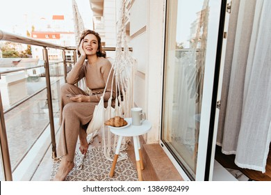 Positive young woman in long dress sitting at balcony with coffee and croissant. Photo of barefooted curly girl enjoying breakfast at terrace.