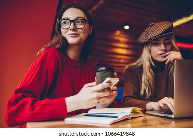 Positive young woman looking away holding coffee cup cooperating with colleague on freelance project, female students learning in cafe interior using modern technology doing homework task together