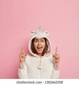 Positive young woman opens mouth, feels pleased, points with fore fingers at upper blank space, wears warm kigurumi pyjamas, advertises something for good sleep, isolated over pink studio wall
