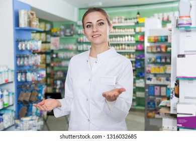 Positive young woman pharmacist in uniform is standing welcoming in pharmacy