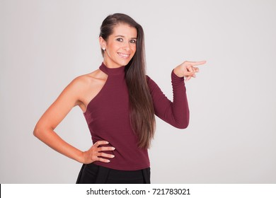 Positive young woman points finger and smiles