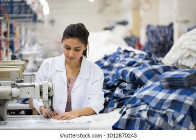 Positive young woman sewing with professional machine at workshop.
