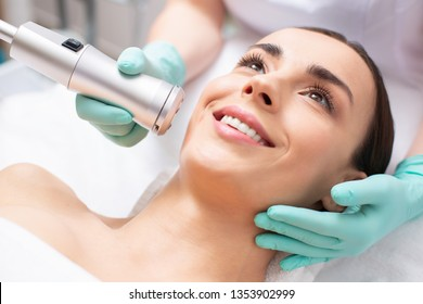 Positive young woman smiling while professional beautician making massage of her face with a special tool during the oxygen meso therapy