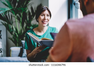 Positive young woman with studying book laughing and talking with friend about literature plot sitting at home interior.Cheerful hipster girl smiling and holding bestseller in hands enjoying hobby