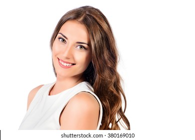 Positive young woman in white dress smiling at camera. Isolated over white background. Beauty concept. Healthy teeth. Cosmetics.