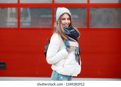 Positive young woman in winter hat in a warm stylish jacket with a scarf in a cage and with a fashionable backpack is standing and smiling against the background of a red metal door.Cheerful nice girl