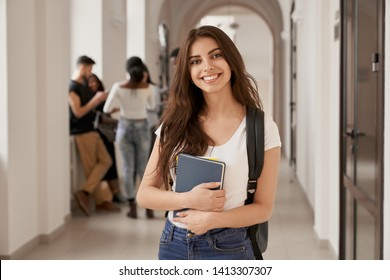 Positivity beautiful girl smiling at camera, standing on corridor with notes as backpack, going to lesson. Happy brunette female student studying in luxury university.