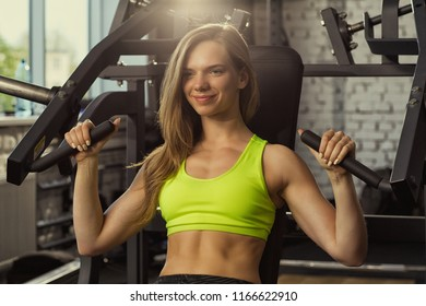 Positivity and happy blondie girl doing arm exercises on metallic block simulator in modern gym. Blondie sportswoman keeping healthy lifestyle, training alone for healthy and slim figure.