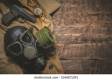 Post apocalypse soldier table concept background. Gas mask, gun, compass and old military wear on aged wooden background.