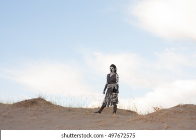 Post apocalyptic humanoid on a desolate dry desert sand dune looking out over a vast wasteland