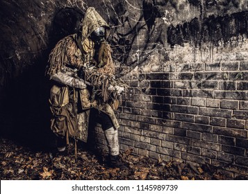 Post apocalyptic survivor, mysterious underground creature, stalker in gas mask and rags with runes, armed with handmade gun, hiding in dungeon, abandoned tunnel or city dark catacombs, sepia toned