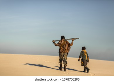 Post apocalyptic woman and boy walking with weapons outdoors. Dead wasteland on the background. Attractive fighter girl warrior in shabby clothes with sword traveling with a brutal kid. A couple of