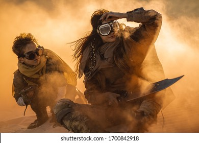 Post apocalyptic woman and boy with weapons outdoors. Desert in smoke and dead wasteland on the background. Aggressive girl warrior in shabby clothes holding sword and young boy with gun and chain