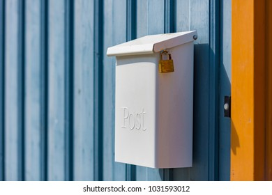 Post box on blue wooden fence. Norway, Scandinavia, Europe.