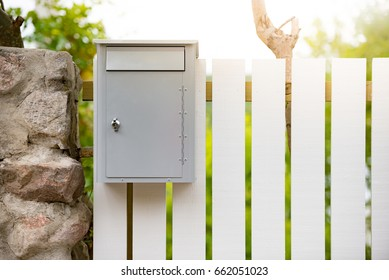 Post box on white wooden fence. Sweden, Scandinavia, Europe.