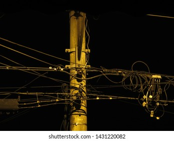 post eletric at night and tangle of wires