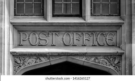 Post Office Carved in Stone above a door, black and white photography shallow depth of field