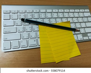 post it and pencil on white keyboard