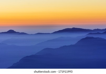 post sunset scene in Mountain valley filled with fog