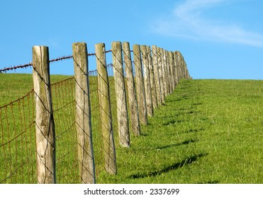 Post and wire fence on a grassy hill