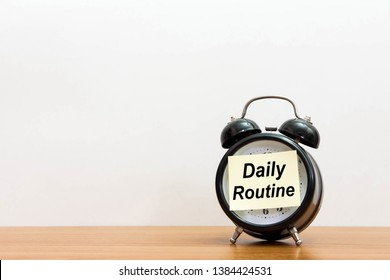 Post it word daily routine alarm clock on wood desk white background.  Sticker notepad paper message daily routine and watch on wooden table for copy space.