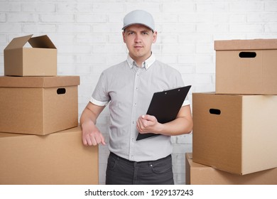 postal delivery or moving day concept - deliveryman in uniform standing between boxes with clipboard in hand