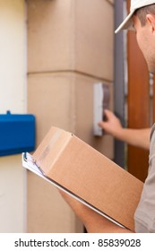 Postal service - delivery of a package; the postman is standing in front of the door and rings the bell