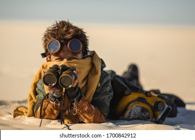 Post-apocalyptic boy with binoculars outdoors. Desert and dead wasteland on the background. Aggressive youn warrior in shabby clothes laying a sand in ambush searching someone. People in nuclear post