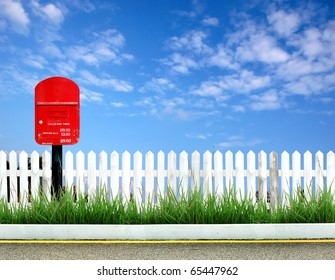 postbox on road side with white fence and blue sky