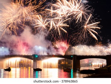 Postcard for 9 may or victory day celebration. Great firework landscape at night with bridge, reflecting light on river surface with drifting boats. Tver, Russia