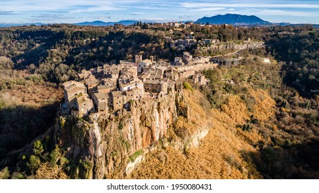 Postcard from Italy. Aerial view of the medieval village of Calcata with its volcanic cliff and the valley of the Treja river with Mount Soratte in the background.