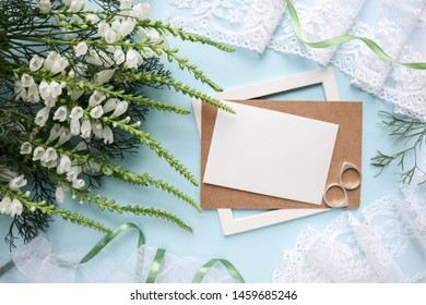 Postcard mockup with white flowers on a blue background and envelope