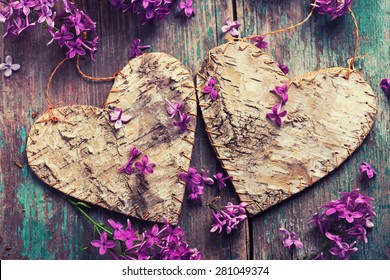 Postcard with two decorative hearts and fresh lilac flowers on green aged wooden background. Selective focus. Toned image.