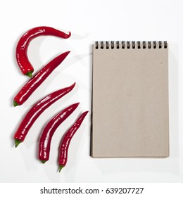 Postcards for recipes. Sketchpad and red hot pepper as a frame on a white background.