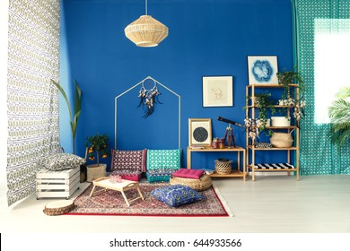 Postcolonial home interior with colorful pattern pillows and wood bookcase