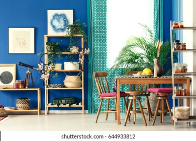 Postcolonial room with wooden bookcase, dining table, chairs, pattern curtain