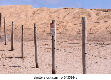 "Posted sign on a wire fence read ""Danger"" and ""Do not go beyond this point"". A protective barrier around dangerous place"