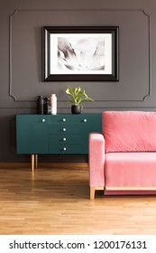 Poster above green cupboard in grey loft interior with pink couch on wooden floor. Real photo