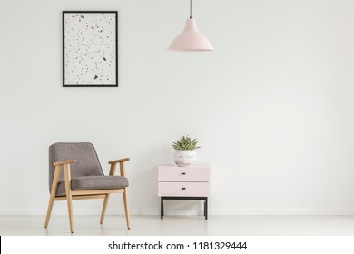 Poster above grey wooden armchair next to cabinet with plant in white flat interior with lamp. Real photo