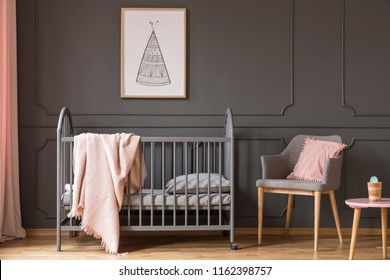 Poster above kid's bed with blanket next to grey armchair with pink pillow in bedroom interior. Real photo