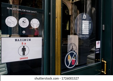A poster advising customers to practise social distancing while shopping at entrance of  retail shop during covid-19 outbreak in Brussels, Belgium, on May 8, 2020