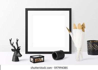 Poster frame mockup square size, front view, with black decor elements, feathers and blank copy space on white background.