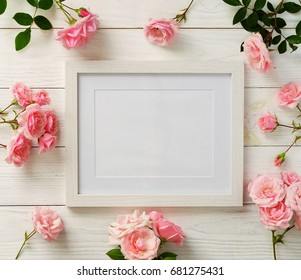 Poster frame mockup, top view, pink roses on white wooden background.Holiday concept.Flat lay. Copy space