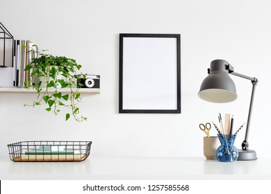 Poster frame over a desk with lamp, ivy and supplies.