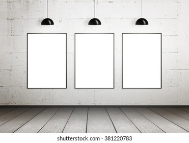 Poster frames isolated for mock up in gallery. Lamps illuminate the wall.