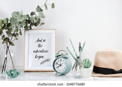 Poster framewith tiped text: Adventure begins, front view, with decor elements and female accessories, flowers and blank copy space over the white wall.