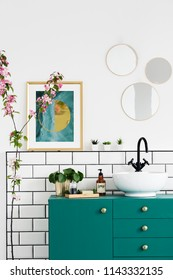 Poster next to mirrors above green cabinet in bathroom interior with pink plant. Real photo
