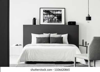Poster on black bedhead of white bed in contrast bedroom interior with grey chair and lamp